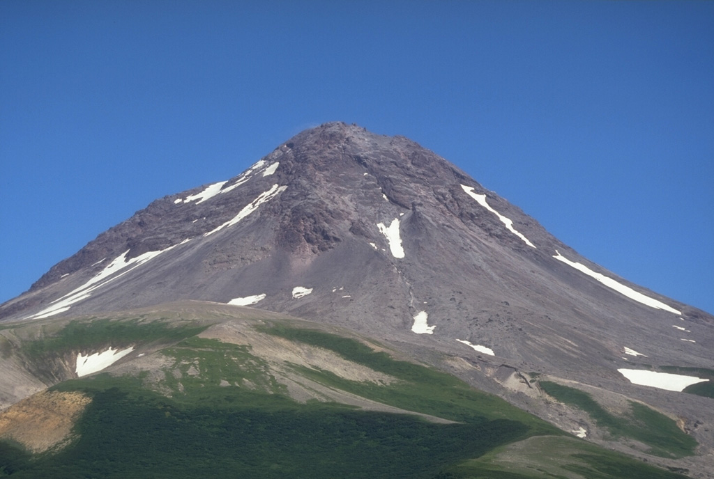 The summit lava dome complex of Augustine volcano is seen here above its SW flank. The upper part of the summit is formed by a lava dome from the 1963-64 eruption. Pre-Augustine sedimentary basement rocks of Jurassic to Tertiary age are exposed on the south flank to an elevation of 320 m. Photo by Game McGimsey, 1994 (Alaska Volcano Observatory, U.S. Geological Survey).