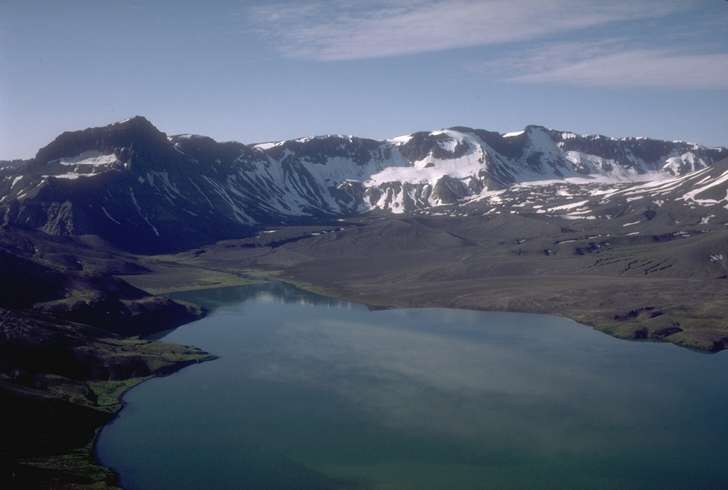 This view looks south across the caldera from the north rim of Aniakchak. Surprise Lake and its outlet are visible at the upper left. The prominent dark peak on the skyline is Black Nose, a high-standing remnant of pre-caldera volcaniclastics. Hummocky ground in the distance against the caldera wall is a pumice-covered glacier and associated moraine. Surprise Lake once covered a much larger part of the caldera floor before catastrophically draining through a notch in the east caldera rim. Photo by Tom Miller, 1985 (Alaska Volcano Observatory, U.S. Geological Survey).