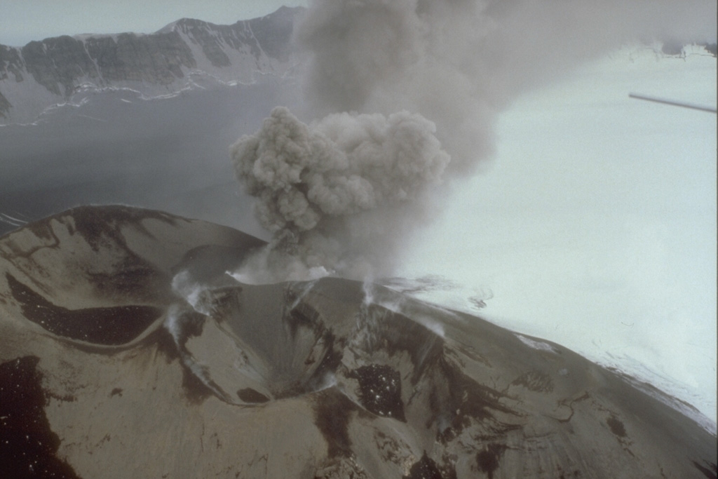 In this 3 August 1993 photo a small ash plume rises from a scoria cone within the Veniaminof caldera. Intermittent explosive eruptions began on 30 July and continued for more than a year. The eruptions also formed a new cone SE of the main western cone. As during the 1983-84 eruption, lava flows erupted onto the ice-covered caldera floor. Ash darkens the left side of the caldera floor in this view, with the caldera wall in the background.  Photo by D. Sellers, 1993 (Alaska Department of Fish and Game).