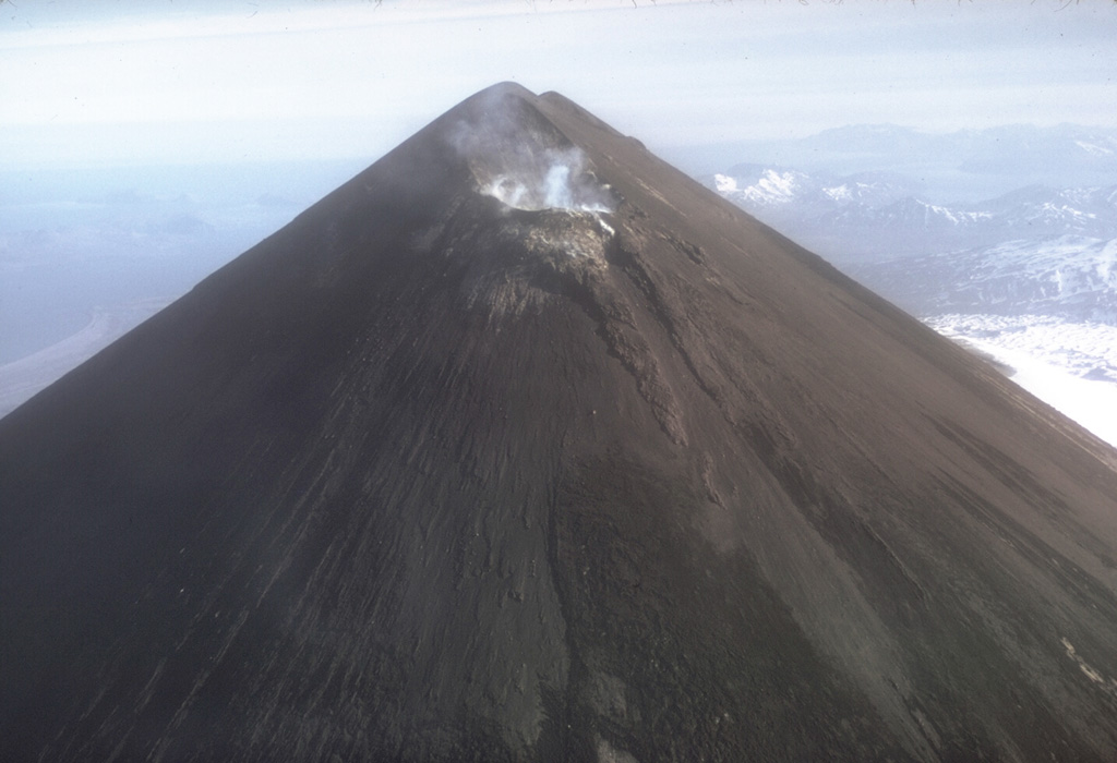 The entire upper flanks of Pavlof are darkened by ash in this November 1973 photo taken after a 12-13 November explosive eruption. Small plumes rise from the crater on the uppermost NE flank just below the normally-snow-covered summit. Photo by Tom Miller, 1973 (Alaska Volcano Observatory, U.S. Geological Survey).