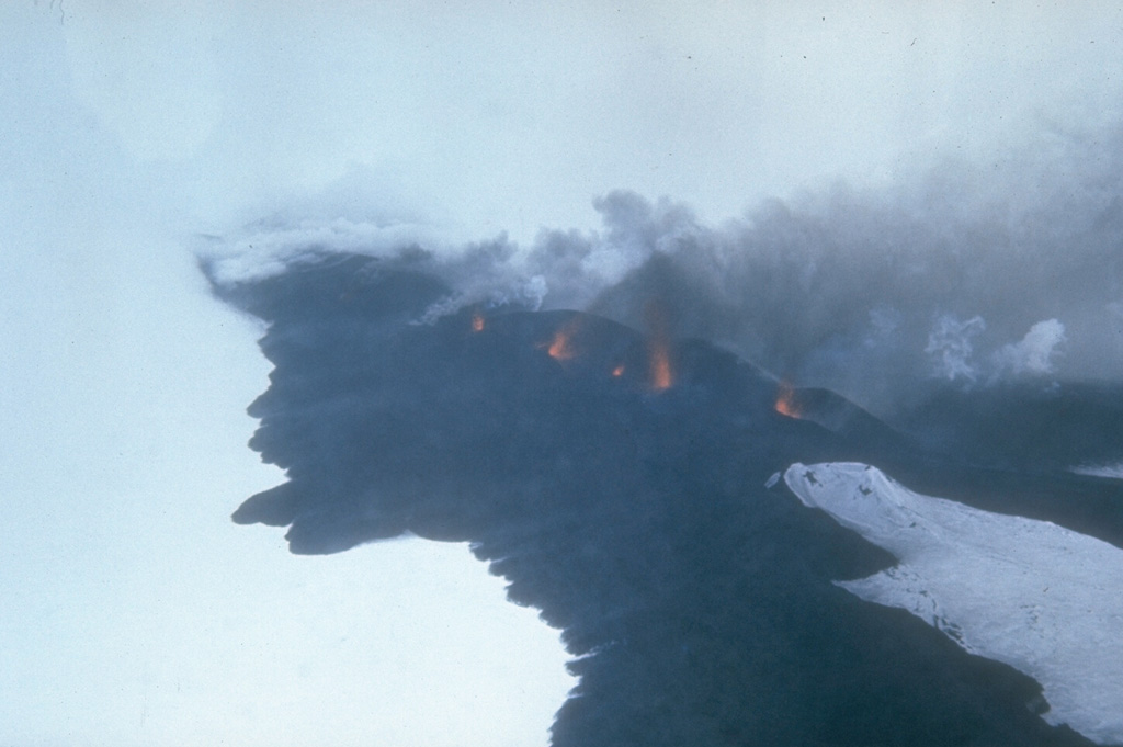 Lava fountains rise above a fissure on Seguam volcano on 8 March 1977. This view from the south shows part of the 1.5-km-long eruptive fissure SE of Pyre Peak. Black lava flows move across the snow from the fissure and diverge around an older cone to the lower right. Pyre Peak, within the westernmost of two calderas, is surrounded by fresh lava fields. Photo by U.S. Coast Guard, 1977 (courtesy of Alaska Volcano Observatory).