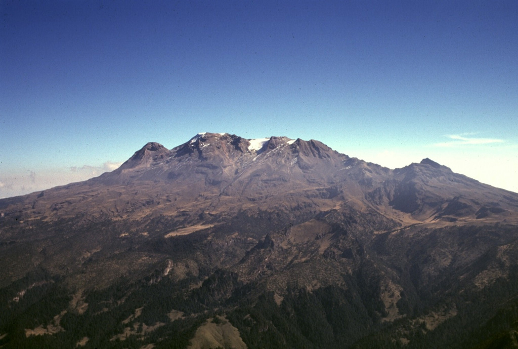 "Iztaccíhuatl, the ""Woman in White,"" presents the profile of a sleeping woman as seen here from the west above the Valley of Mexico.  A series of overlapping cones constructed along a NNW-SSE line to the south of the Pleistocene Llano Grande caldera forms the summit ridge.  From left to right they are La Cabeza (the head), El Pecho (the breast), Las Rodillas (the knees; at the end of the central summit ridge), and Los Pies (the feet).  The volcano is mostly Pleistocene in age, but minor Holocene activity has occurred.   Photo by Gerardo Carrasco-Núñez (Universidad Nacional Autónoma de México)."