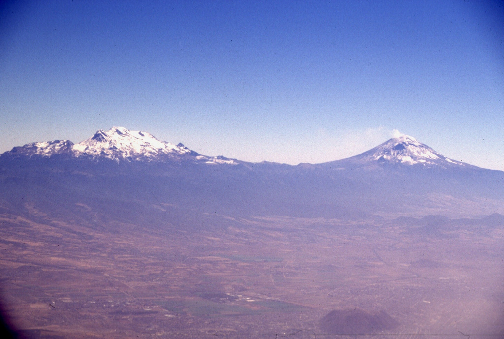 The twin volcanoes of Iztaccíhuatl (left) and Popocatépetl dominate the landscape east of the Valley of Mexico.  The differing profiles of the two volcanoes, the 2nd and 3rd highest in México, reflect the varying styles and durations of volcanism.  Iztaccíhuatl's elongated form reflects migration of volcanism over long periods of time along a NNW-SSE trend; it is largely Pleistocene in age, and has been extensively eroded.  Symmetrical Popocatépetl is much younger and has more-localized vents.  It has erupted frequently since the beginning of the Spanish era. Photo by Lee Siebert, 1997 (Smithsonian Institution).