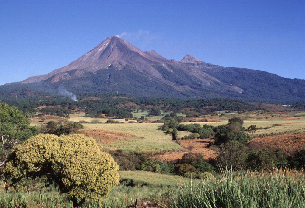 Colima (left), with a plume of whispy steam drifting from its summit, and Nevado de Colima (right) form a pair of N-S-trending stratovolcanoes composing the Colima volcanic complex.  The modern Colima cone was constructed during the past 2600 years within a large horseshoe-shaped caldera breached to the south that was formed by edifice collapse.  The modern edifice has overtopped the eastern caldera rim (roughly corresponding to the vegetation line), and unvegetated lava flows erupted during 1975-76 spill down its outer flanks.  Photo by Lee Siebert, 1997 (Smithsonian Institution).