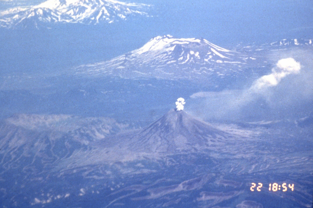 An aerial view from the SW on 22 July 1996 shows an ash plume rising above the summit crater of Karymsky with Maly Semyachik behind it. The 1996 eruption began on 2 January simultaneously with an eruption at nearby Akademia Nauk caldera, out of view to the right. The Akademia Nauk eruption lasted only a day, but long-term eruptions continued at Karymsky.  Photo by Phillip Kyle, 1996 (courtesy of Vera Ponomareva, Institute of Volcanic Geology and Geochemistry, Petropavlovsk).