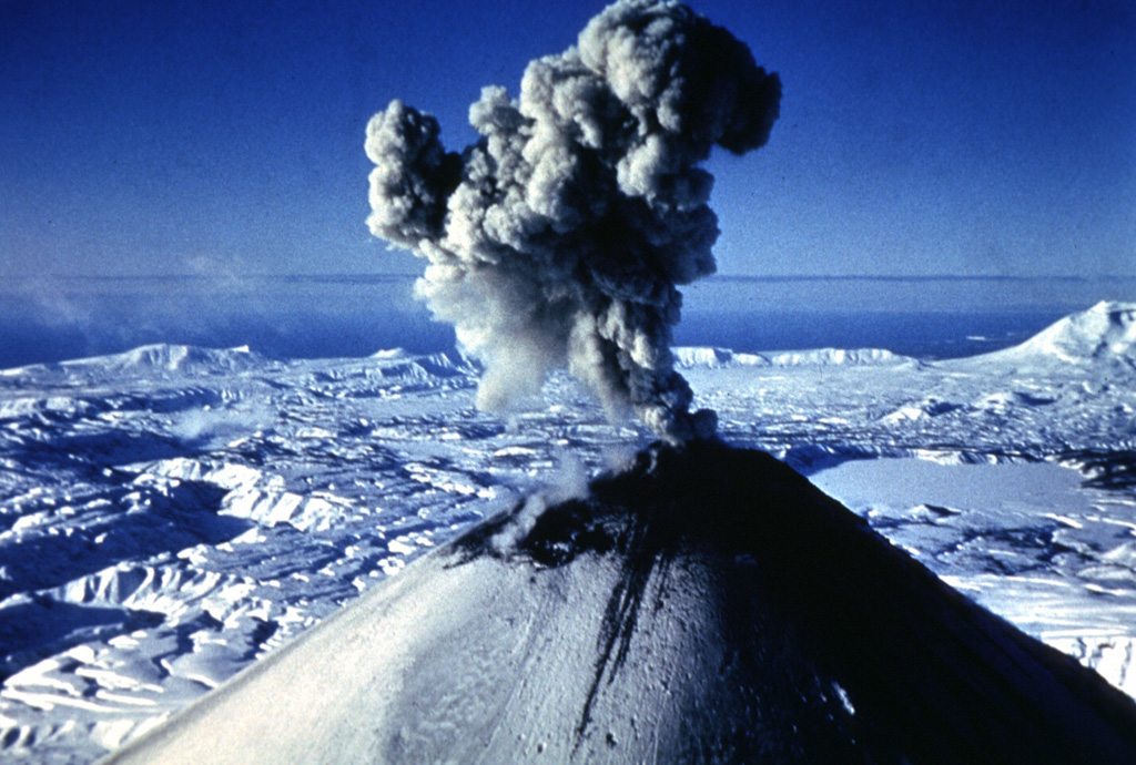 An ash plume rises above the summit of Karymsky in January 1996. Explosive eruptions began on 2 January from the summit and SW flank. On the same day a powerful explosive eruption took place from Akademia Nauk caldera, the smooth area to the right. The Akademia Nauk eruption lasted only a day, but long-term activity continued at Karymsky. Photo by Nikolai Smelov, 1996 (courtesy of Vera Ponomareva, Institute of Volcanic Geology and Geochemistry, Petropavlovsk).