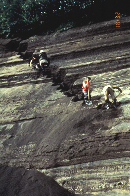 Volcanologists from the Institute of Volcanic Geology and Geochemistry in Petropavlovsk and the New Mexico Institute of Mining and Technology excavate a section through layered tephra deposits from Ilyinsky volcano in southern Kamchatka. Detailed study of the products of individual eruptions are used to determine the timing, frequency, and magnitude of those eruptions. The sequence of tephra layers shown here was deposited by explosive eruptions from Ilyinsky during the last 5,000 years. Photo by Phil Kyle, New Mexico Institute of Mining and Technology, 1996 (courtesy of Vera Ponomareva, IUGG, Petropavlovsk).