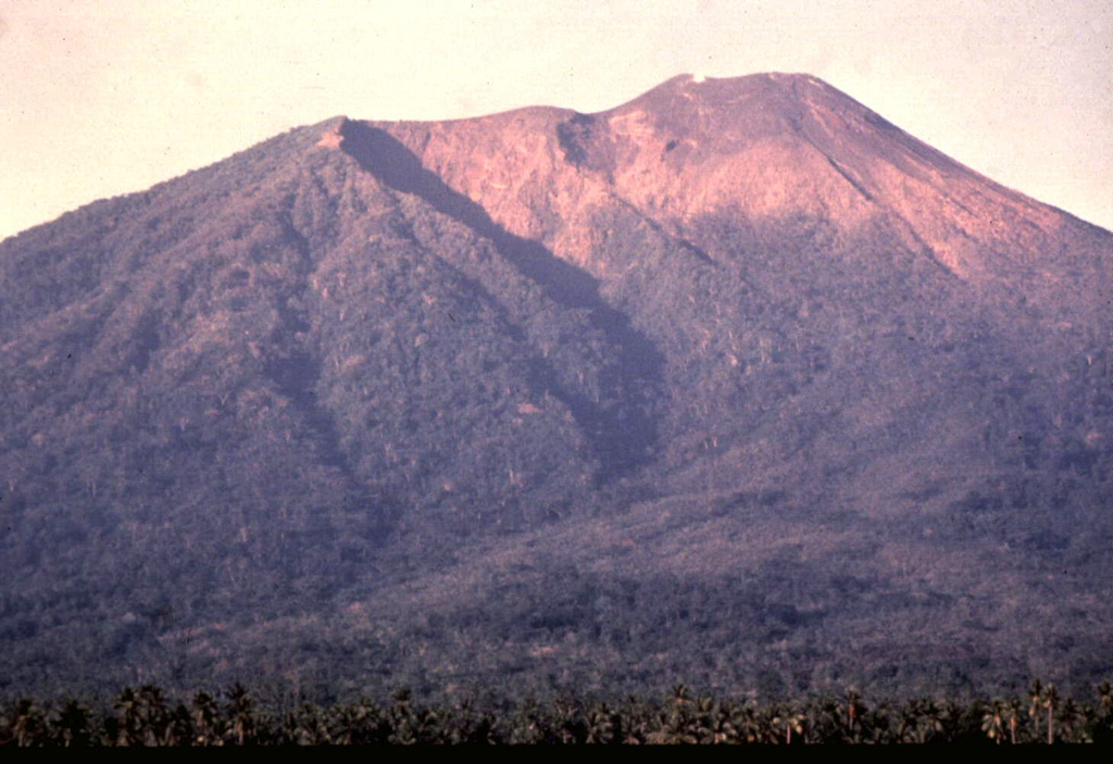 The three craters forming the summit of Gamalama volcano are visible in this view from the NE flank.  The craters have migrated to the north, with the modern cone (right) forming the present summit of the volcano.  The prominent shadow cutting diagonally to the right marks the rim of the older GI crater, inside of which the GII cone and crater grew.  The GIII crater truncates the flat-topped summit of Gamalama. Photo by Jack Lockwood, 1980 (U.S. Geological Survey).