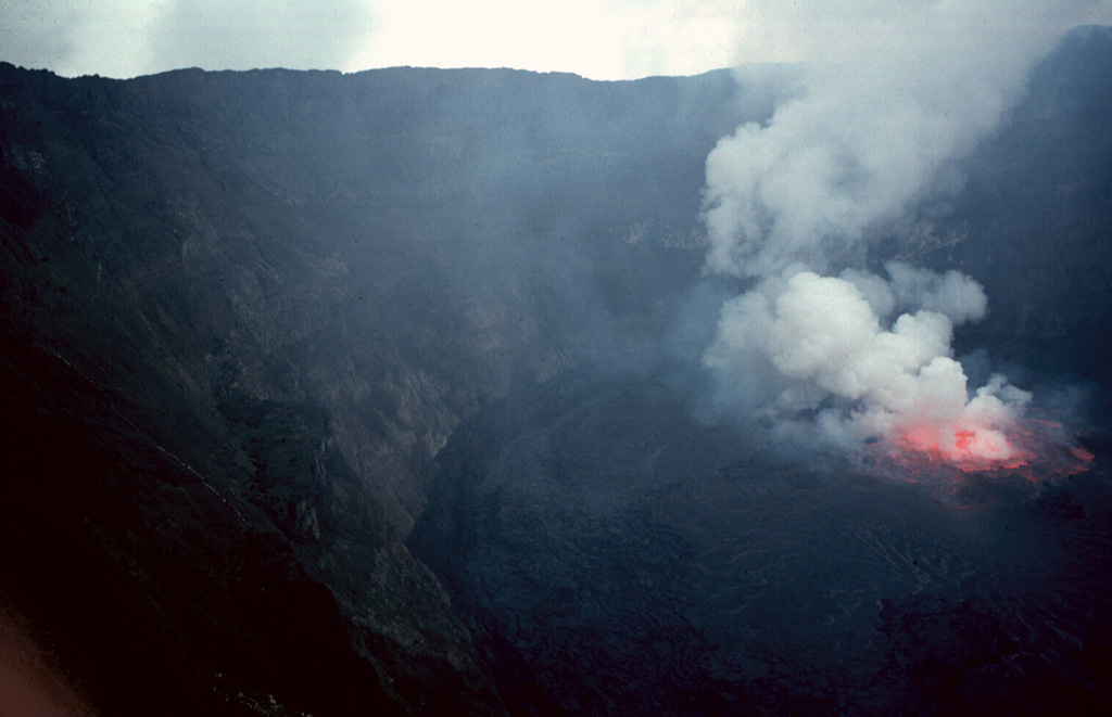 A gas plume rises above lava fountains in a lava lake in the summit crater of Nyiragongo volcano on 20 August 1994. Renewed lava-lake activity began the night of 23-24 June 1994 and continued into the fall of 1996. By August 1995 the surface of the lava lake had risen 50 m. Photo by Jack Lockwood, 1994 (U.S. Geological Survey).