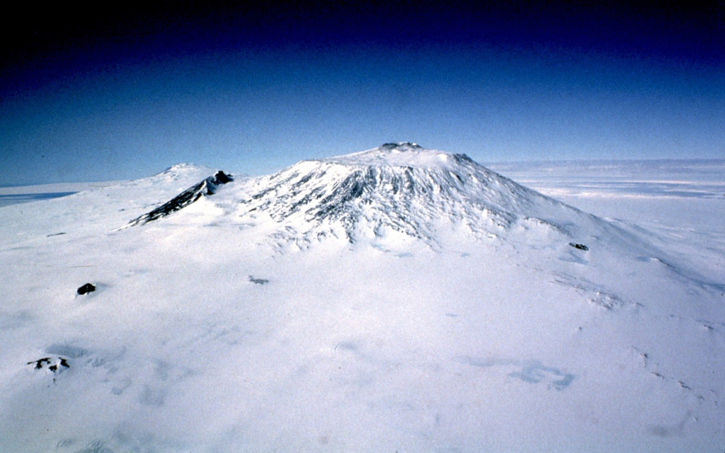 Mount Erebus, seen here from the west, is Earth's southernmost historically active volcano.  The 3794-m-high peak is Antarctica's highest Quaternary volcano.  A largely filled caldera forms a flat plateau at the summit above which the modern cone was constructed.  Fang Ridge is the dark area on the NE (left) flank of Erebus, and Mount Terror, a large Pleistocene volcano on Ross Island, is visible on the left horizon. Photo by Bill Rose, 1983 (Michigan Technological University).