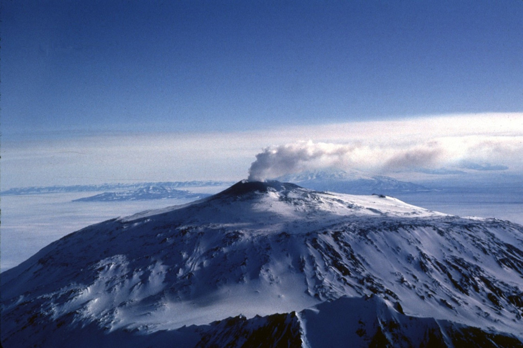 A vigorous steam plume rises above the summit crater of Mount Erebus in 1983.  Fang Ridge appears in the foreground of this view from the NE.  The flat summit plateau cutting across the center of the photo marks the rim of a caldera, inside which the active summit cone was constructed. Photo by Bill Rose, 1983 (Michigan Technological University).