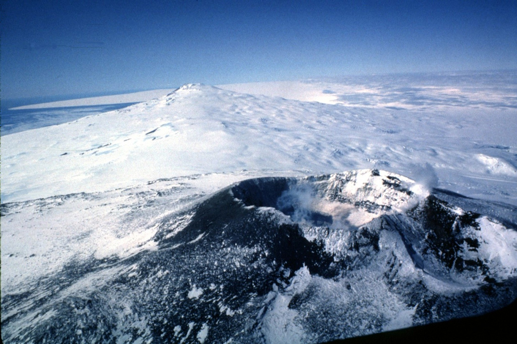 Two of the three volcanoes forming Ross Island are seen in this aerial view from the west.  The summit crater of historically active Mount Erebus appears in the foreground, with glacier-covered 3230-m-high Mount Terror in the distance.  Mount Terror is a large basaltic shield volcano of Pleistocene age.  Numerous satellitic cinder cones and lava domes are scattered over its flanks.  The summit crater of Mount Erebus contains an active lava lake. Photo by Bill Rose, 1983 (Michigan Technological University).