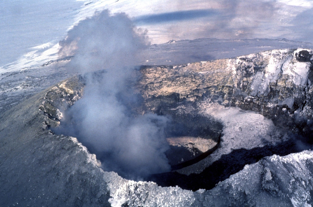 A steam plume rises above an active lava lake in the summit crater of Erebus volcano in December 1983.  The currently active lava lake at Erebus was first observed on December 24, 1972.  Lava-lake activity accompanied by intermittent strombolian eruptions has been observed during annual scientific expeditions since then.  The active lava lake is located at the bottom of an inner 100-m-deep crater, whose flat, snow-covered rim forms a bench at the right (SW) side of the Main Crater. Photo by Bill Rose, 1983 (Michigan Technological University).