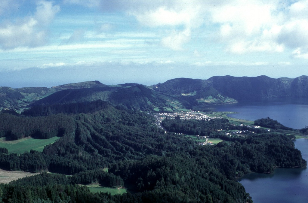 A nearly circular ring of six Holocene pyroclastic cones occupies the floor of 5-km-wide Sete Cidades caldera.  These have been the source of a dozen trachytic pumice-fall deposits erupted during the past 5000 years.  Three of these forested cones appear in this view from the southern caldera rim, Caldeira Seca (extreme left), Caldeira do Alferes (left-center), and Seara (right center).  The cones were constructed on the caldera floor adjacent to the two lakes of Lagoa Azul (top right) and Lagoa Verde (bottom right).  Photo by Rick Wunderman, 1997 (Smithsonian Institution).