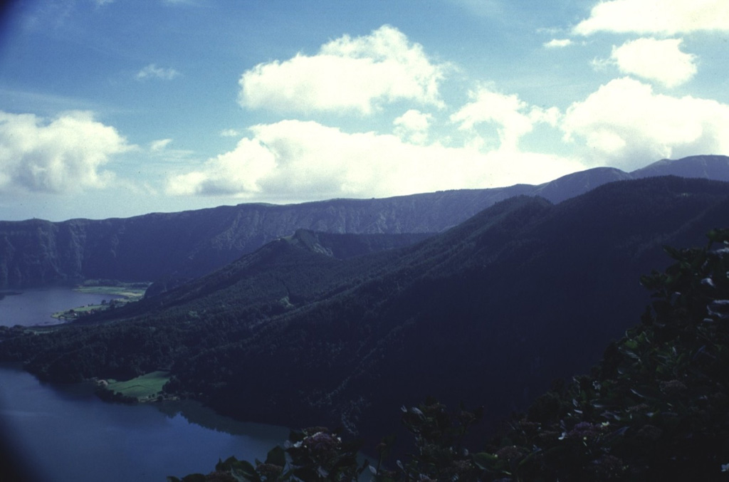 The SE floor of Sete Cidades caldera contains a large trachytic lava dome that is cut by two lake-filled craters.  The rim of Lagoa de Santiago crater is visible at the center, to the right of the Lagoa Azul and Lagoa Verde lakes occupying the caldera floor.  The Lagoa Rasa crater rim appears at the extreme right, below the rim of Sete Cidades caldera.  Lagoa de Santiago was the source of a major explosive eruption about 1900 years ago, and Lagoa Rasa erupted several centuries later. Photo by Rick Wunderman, 1997 (Smithsonian Institution).