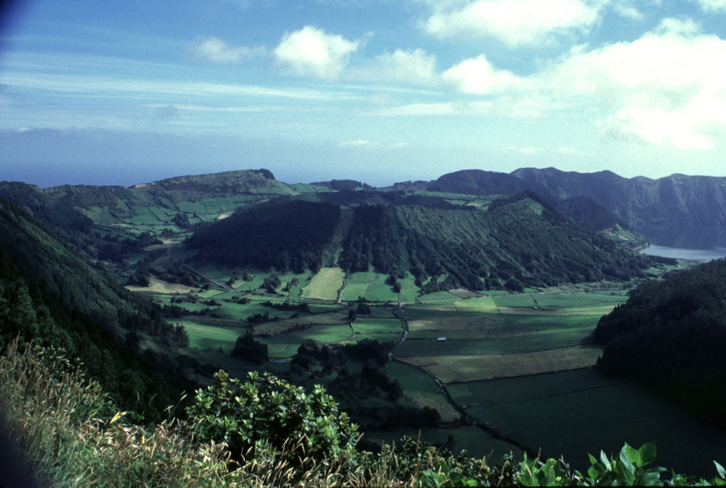 Caldeira do Alferes (center) is one of a group of six pyroclastic cones constructed on the floor of Sete Cidades caldera.  The adjacent cone of Seara appears to the right of Caldeira do Alferes in this view from the western caldera rim.  Strong eruptions of trachytic pumice occurred a dozen times during the past 5000 years from Sete Cidades, one of the most active volcanoes of the Azores. Photo by Rick Wunderman, 1997 (Smithsonian Institution).