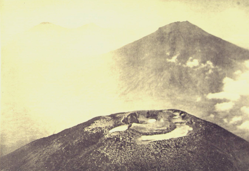 An aerial view from the NW looks across the summit crater complex of Gunung Sundoro volcano towards Gunung Sumbing. These roughly 3,000-m-high volcanoes form prominent landmarks between the Dieng volcanic complex and the city of Yogyakarta. Both volcanoes have erupted in historical time. Photo published in Taverne, 1926