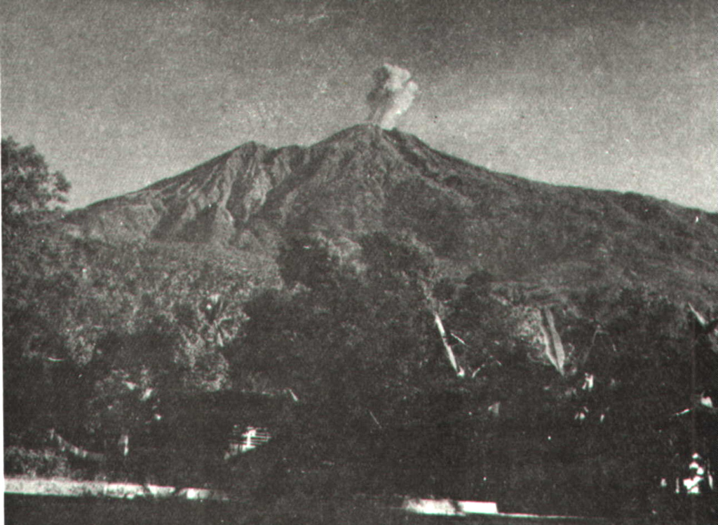 An eruption plume above the summit of Karengetang (Api Siau) volcano is seen from Ulu village on the northern flank sometime during 1961.  Explosive eruptions in that year began on February 28 and lasted until April.  Incandescent material was ejected to 300 m above the vent and the eruption plume rose 1.5 km above the crater.  Explosive activity also occurred in October 1961. Photo by M. Pantauw, 1961 (published in Kusumadinata 1979,