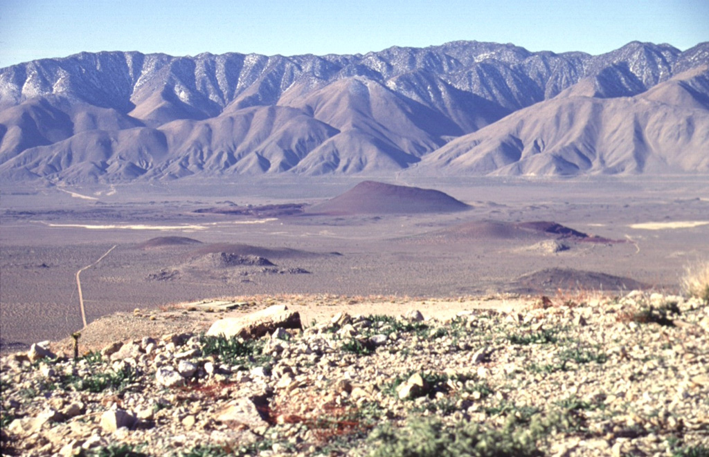 Red Cone (center) is the largest of a group of isolated basaltic scoria cones and lava flows on the floor of the Rose Valley in the western part of the Coso volcanic field.  The late-Pleistocene scoria cone is seen here from the NE, with the towering fault scarp of the Sierra Nevada Range in the background.  Highway 395 traverses Rose Valley between the cone and the Sierras.    Photo by Lee Siebert, 1997 (Smithsonian Institution).