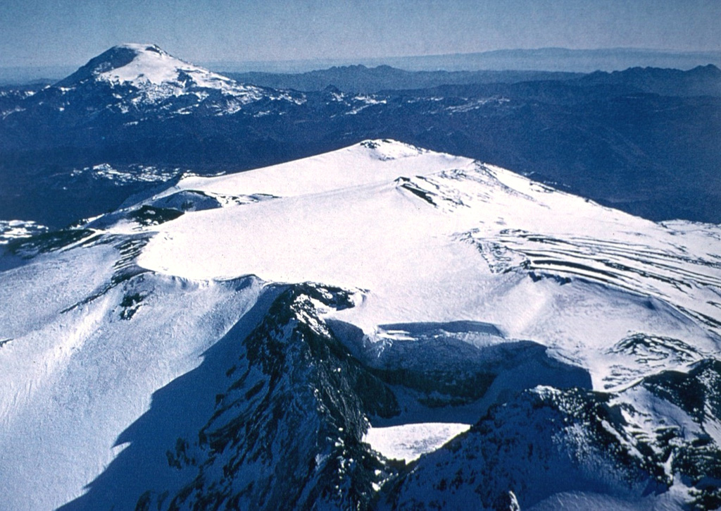 The broad glacier-covered summit of Volcán Copahue along the Chile/Argentina border is seen from the SE with conical Callaqui volcano in the distance.  The lake-filled active crater of Copahue (lower center) has been the site of historical eruptions.  The composite cone was constructed along the Chile/Argentina border within an 8-km-wide caldera formed 0.6 million years ago.  The eastern summit crater is part of a 2-km-long, ENE-WSW line of nine craters that cuts across the western rim of the caldera. Photo by Oscar González-Ferrán, 1992 (University of Chile).