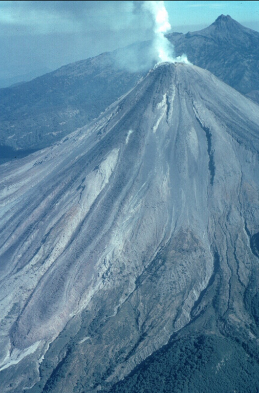 A northward-looking helicopter view of Colima volcano on February 8, 1999 shows the steaming lava dome and active lava flows with Nevado de Colima in the background.  A single flow originated from the summit dome, but the light-colored topographic high on the upper SW flank caused the block lava flow to split into separate lobes.  The easternmost lobe can be seen here descending diagonally to the lower left, with other lobes farther to the left.  The lava flow from 1991 was completely covered by the new lava.  Photo by Jim Luhr, 1999 (Smithsonian Institution).