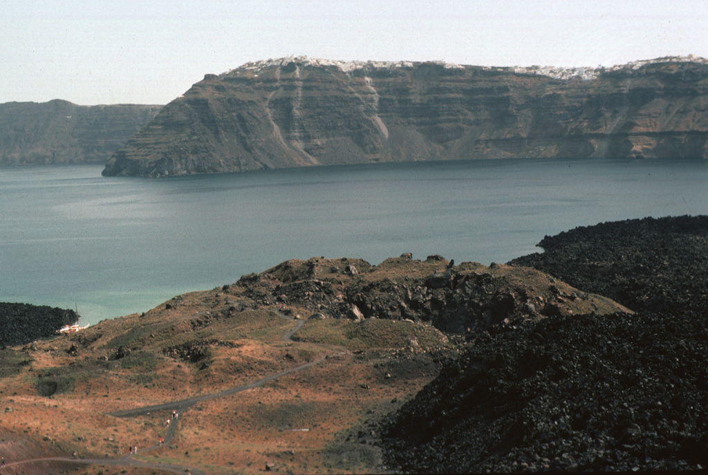 The crater in the foreground was formed during an eruption from 1570-1573 CE. Initially submarine eruptions were followed by the formation of the new island of Mikri Kameni (Little Burnt Island) NE of Palaea Kameni Island. The 1570-73 eruption created a small island with a diameter of about 400 m and a height of 70 m, topped by a 20-m-deep crater. The western wall of Santorini's caldera appears in the background, capped by the houses of the village of Merovígli. Photo by Lee Siebert, 1994 (Smithsonian Institution)