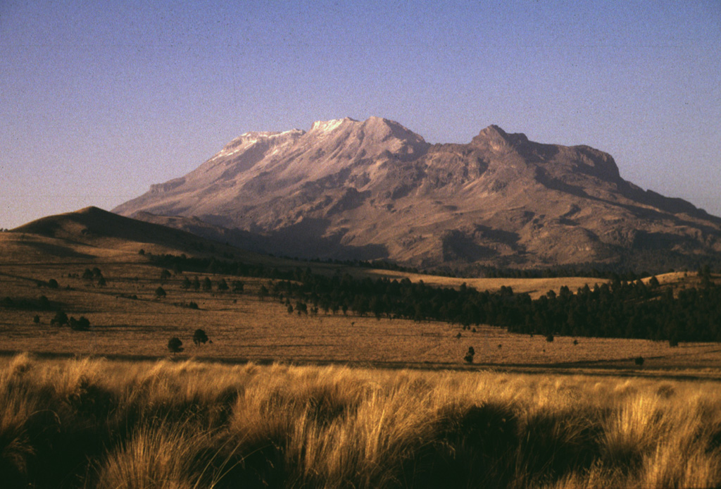The broad Iztaccíhuatl massif rises north of Paso de Cortes, the 3680-m-high saddle between Iztaccíhuatl and Popocatépetl volcanoes.  The conquistador Cortés crossed the pass, from where he first saw Tenochtitlán, the Aztec capital.  The summit of Iztaccíhuatl is at the left, NNW of the apparent high point Las Rodillas (center).  The sharp peak at the right is Los Pies (also known as Amacuilecatl), the southernmost major peak of the volcano. Photo by Lee Siebert, 1998 (Smithsonian Institution).