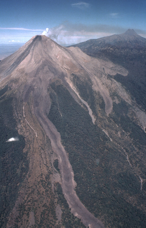The 3.5-km-long lava flow erupted in 1975-76 descended to beyond the bottom of the photo.  The flow split into two lobes on the upper flank; a shorter lobe drops diagonally to the right just below the light-colored barranca wall (center).  Another flow during this eruption traveled down the NE flank and diverged around El Volcancito, the lava dome forming the shoulder on the NE (right-hand) flank of Colima. The southern lobe of this flow can be seen to the right of the light-colored barranca.  A steam plume drifts to the NE toward the summit of Nevado de Colima. Photo by Bill Rose, 1989 (Michigan Technological University).