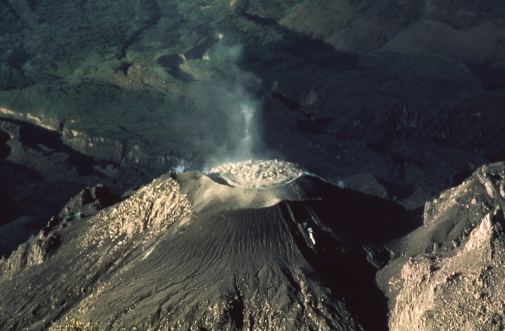 A blocky lava dome fills the crater of the Caliente vent of Santiaguito lava dome in 1988, as seen from the summit of Santa María volcano.  Slow growth of the plug dome was accompanied by periodic explosive eruptions that ejected ash columns to about 1.5 km heights without disrupting the dome. Photo by Jon Fink, Arizona State University, 1988 (courtesy of Bill Rose, Michigan Technological University).