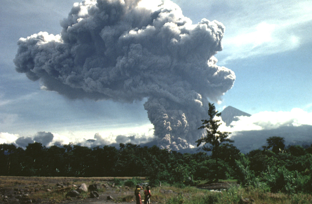 A large pyroclastic flow sweeps down the flank of Santiaguito lava dome on July 19, 1989.  The pyroclastic flow and ash column are seen here from just west of El Palmar (10 km south of the dome) about 5 minutes after the start of the explosion.  The summit of Santa María volcano is visible immediately to the right of the ash column, which rose to 4 km above the vent.  The pyroclastic flow traveled 5 km down the Río Nimá and was perhaps the largest since the major 1929-34 activity.    Photo by Mike Conway, 1989 (Michigan Technological University).
