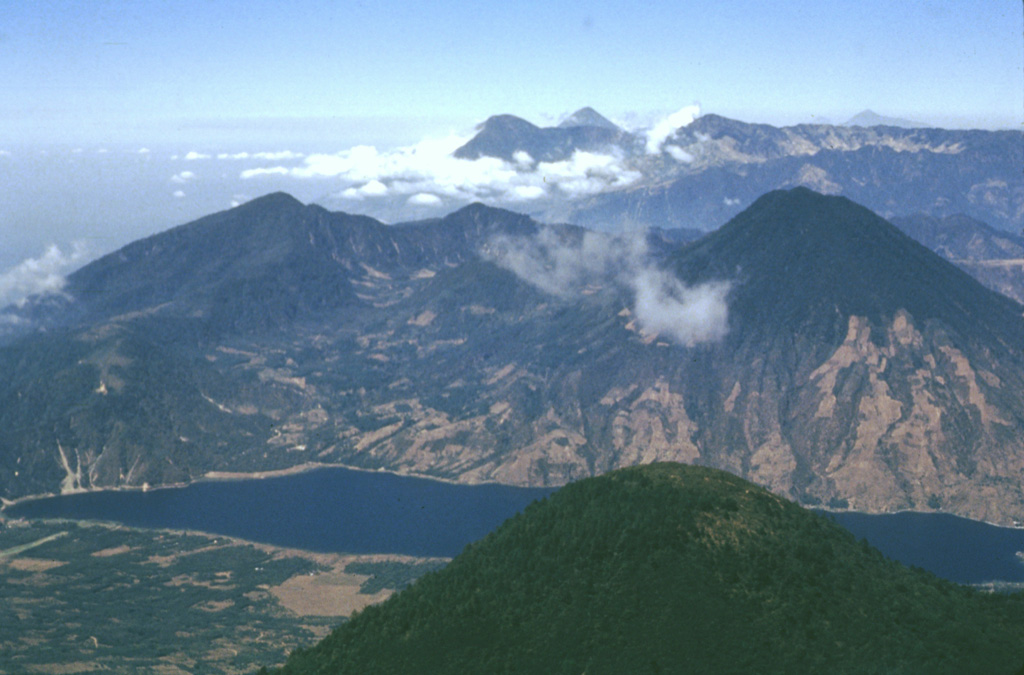 The rounded peak in the foreground is the southernmost of the twin summit peaks of Tolimán volcano.  The older post-caldera volcano of Atitlán caldera, San Pedro, lies across Santiago Bay at the right.  On the center horizon are the peaks of Santo Tomás (left) and Santa María (right).  Tajumulco volcano, Central America's highest, is the peak on the far right horizon.  The Guatemalan volcanic front rises more than 3500 m above the hazy Pacific coastal plain at the upper left. Photo by Bill Rose, 1980 (Michigan Technological University).