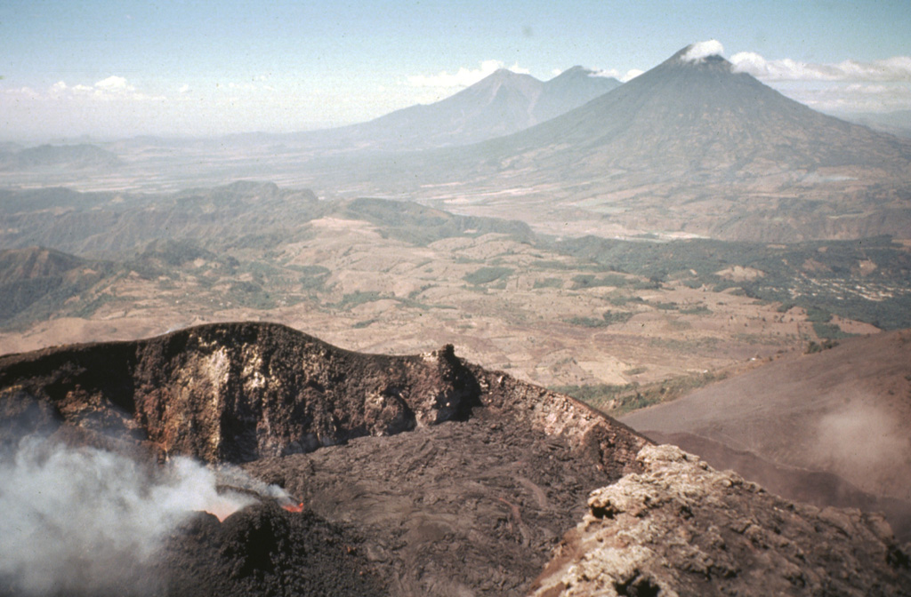 Steam pours from incandescent spatter cones that fed lava flows blanketing the floor of MacKenney crater of Pacaya volcano.  In May 1981, at the time of this photo, the broad several-hundred-meter wide crater rim lay well below the summit of the cone.  From May 9 to June 2 lava flows from the spatter cones covered the crater floor and spilled over a notch in the NW crater rim.  In the background are the twin volcanoes of Fuego and Acatenango (right-center) and the conical Agua volcano (right).  Photo by Bill Rose, 1981 (Michigan Technological University).