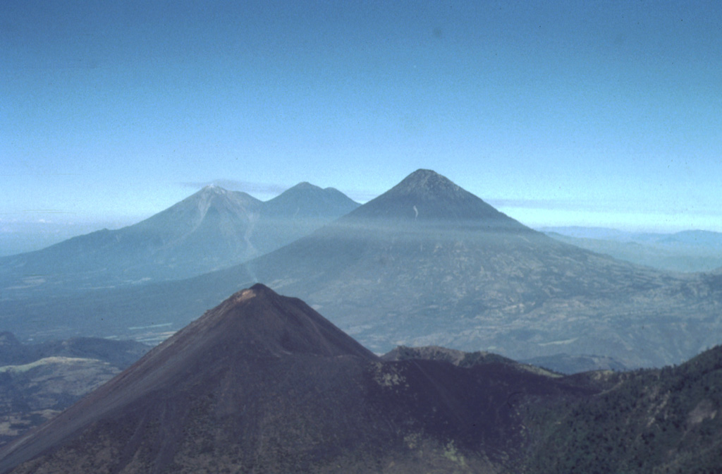 A spectacular aerial view from the east shows four major volcanoes located within 45 km of Guatemala City.  In the foreground is Pacaya, which has been in frequent eruption since 1965.  The modern cone (left-center) partially overlaps the rim of a large caldera.  The massive conical volcano at the right-center horizon is Volcán de Agua, the only one of the four not to have erupted in historical time.  The twin volcanoes of Acatenango (right) and Fuego (left) lie behind Agua.  These latter three volcanoes overlook the historical city of Antigua Guatemala. Photo by Bill Rose, 1991 (Michigan Technological University).