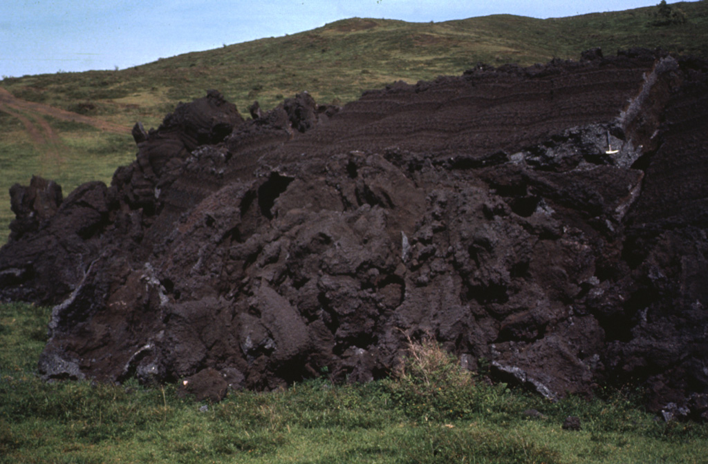 The toe of the 1972 lava flow ends on grassy slopes on the southern flank of MacKenney cone.  Broken slabs mark the flow front.  The rock hammer at the upper right provides scale next to a spectacular grooved lava surface on the top of the flow front that formed when still-fluid lava was squeezed through an irregular crack in previously solidified crust.   Photo by Bill Rose, 1972 (Michigan Technological University).
