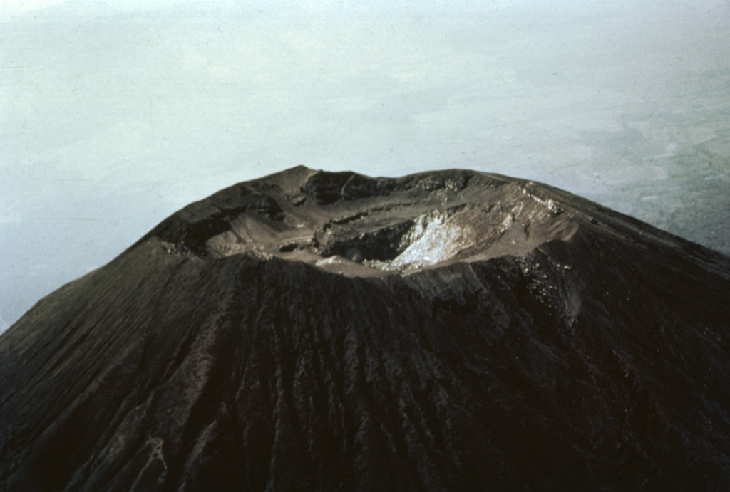 The summit of San Miguel volcano was reported to be peaked prior to the 16th century, but now is truncated by a 1-km-wide crater.  This aerial view shows the 2130 m high point on the far NE crater rim in the center of the photo and several benches cut by a roughly 250-m-deep central crater.  The morphology of the crater has varied greatly during historical time as a result of the creation and subsequent destruction of new craters.  A cinder cone that formed in the NE part of the crater in 1884 had disappeared 50 years later.   Photo by Willard Parsons, 1964 (courtesy of Bill Rose, Michigan Technological University).