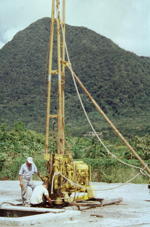 This drill rig on the floor of El Valle de Antón caldera is part of a major geothermal exploration program at El Valle volcano.  In the background to the north is Cerro Gaital, the highest of three post-caldera lava domes constructed along the northern caldera rim. Photo by Paul Kimberly, 1998 (Smithsonian Institution).