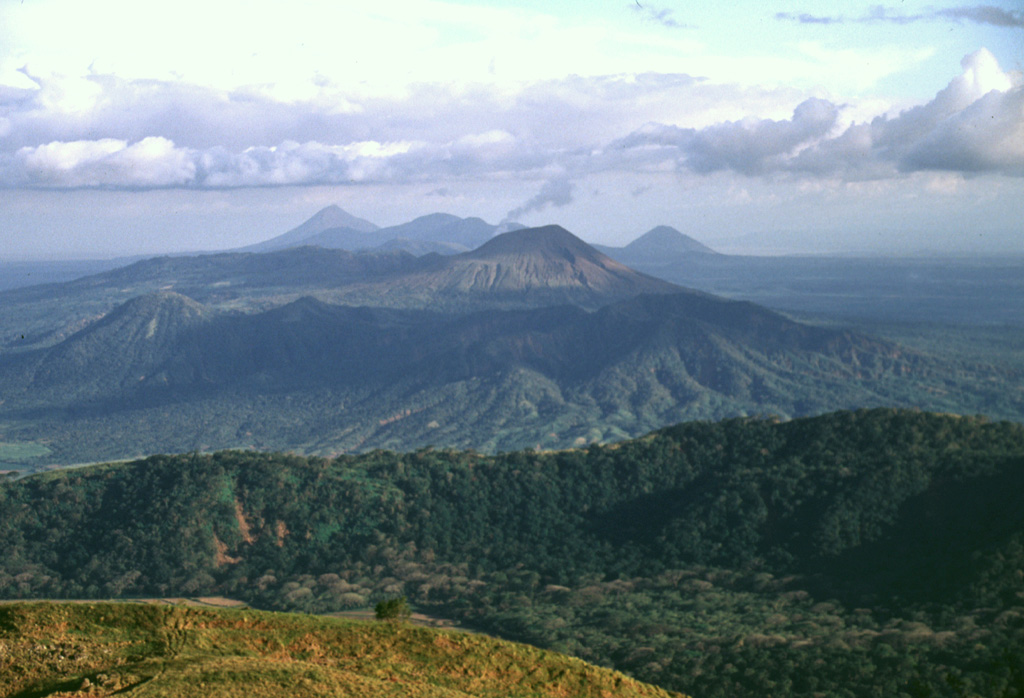 A view from Casita volcano to the SE along the Marrabios Range shows the Telica volcanic complex covering much of the center of the photo.  A thin steam plume rises from the summit of Telica itself (right-center), while the cone of Cerro de Aguero lies at the left-center, with shadows defining older, more dissected parts of the Telica complex.  The forested ridge of La Pelona caldera (part of the San Cristóbal complex) cuts across the lower part of the photo, while Momotombo (left), Las Pilas, and Cerro Asososco (right) lie on the horizon. Photo by Lee Siebert, 1998 (Smithsonian Institution).