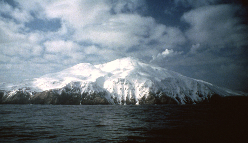 A steam plume rises from the summit of Kiska, one of the westernmost historically active volcanoes of the Aleutian Arc. Three sides of the volcano, including the northern side seen here, are bounded by steep cliffs up to 450 m high. A scoria cone on the flank formed in 1962 at the northern coast. Photo by E.V. Kleff, 1985 (U.S. Fish & Wildlife Service, courtesy of Alaska Volcano Observatory).