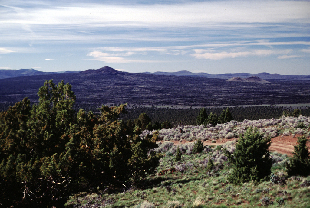 The Late-Pleistocene or early Holocene Squaw Ridge lava field consists of a shield volcano capped by the Lava Mountain pyroclastic cone complex (right-center horizon), which forms a prominent topographic high in this view from Green Mountain.  The Squaw Ridge lava field (also known as the East lava field) is the middle of a group of three young basaltic fields located in the High Lava Plains SE of Newberry volcano.  Lava flowed in all directions for distances up to 6 km from the summit cone complex, surrounding older cones such as those at the far right.  Photo by Lee Siebert, 2000 (Smithsonian Institution).