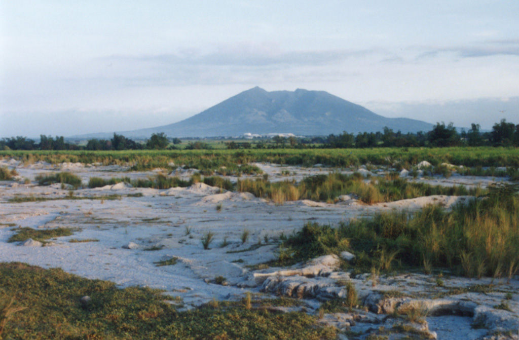 Arayat, seen here from the SW near the city of Angeles, is one of the few topographic features that rise above the flat Central Plain of Luzon Island. A broad valley can be seen here cutting the western flank of the volcano. There are no reports of historical eruptions from Arayat. Photo by Ichio Moriya (Kanazawa University).