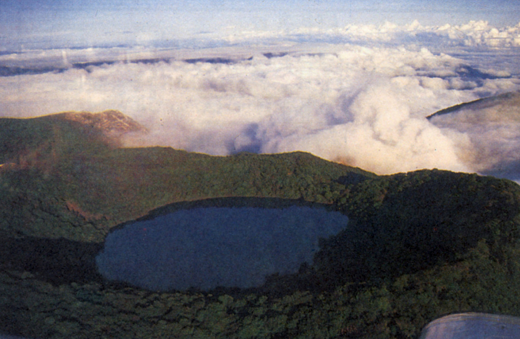 Botos cone forms the 2708 m high point of the Poás volcanic massif.  It was the eruptive focus prior to about 7500 years ago, when that focus shifted to the presently active crater (which lies beneath the clouds to the NW).  The 1-km-wide Botos maar is filled by a 400-m-wide coldwater lagoon sometimes known as Laguna del Fría or Laguna del Poás.  The lake has a maximum depth of 14 m.  The cold, freshwater lagoon contrasts with the hot, extremely acidic lake of the main crater. Photo by S. Mora, 1988 (courtesy of Guillermo Alvarado, Instituto Costarricense de Electricidad).