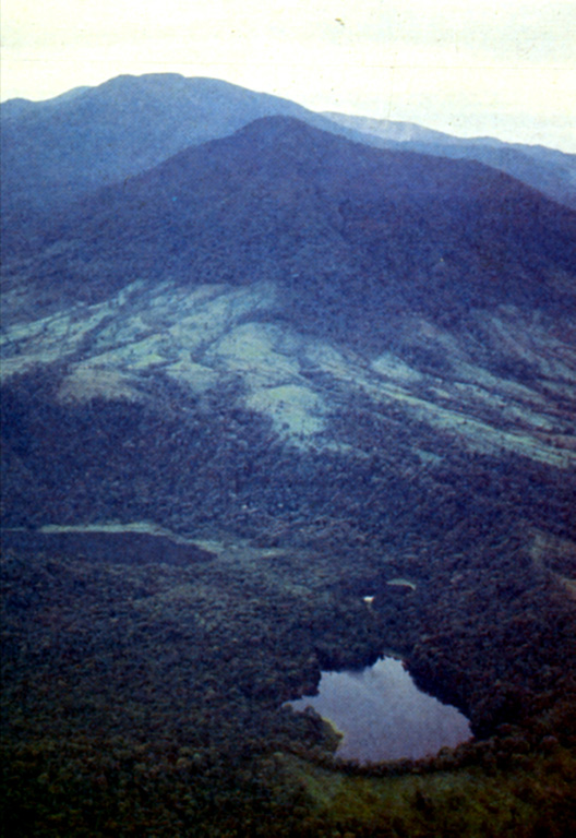An aerial view from the north looks down the chain of vents extending north from Poás volcano.  In the foreground is the Bosque Alegre (Laguna Hule) maar complex, and the forested peak in the middle distance is Cerro Congo volcano.  Poás volcano forms the horizon, about 12 km to the south.  The Bosque Alegre complex contains three lagoons, Laguna Congo (lower right), a small unnamed one above it, and Laguna Hule (left center).  The 2-km-wide complex last erupted about 2730 years ago. Photo by Guillermo Alvarado, 1987 (Instituto Costarricense de Electricidad).