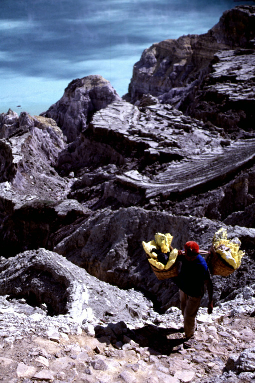 A sulfur miner carries baskets of elementally pure sulfur from a geothermal area near the shore of Kawah Ijen lake in eastern Java. Large blocks of sulfur are broken off and carried out of the crater in baskets before being transported to a sulfur mill on the SE flank of the Ijen caldera. The perspective in this view from near the SE crater lake rim looks down on the surface of the crater lake. Photo by Lee Siebert, 2000 (Smithsonian Institution).
