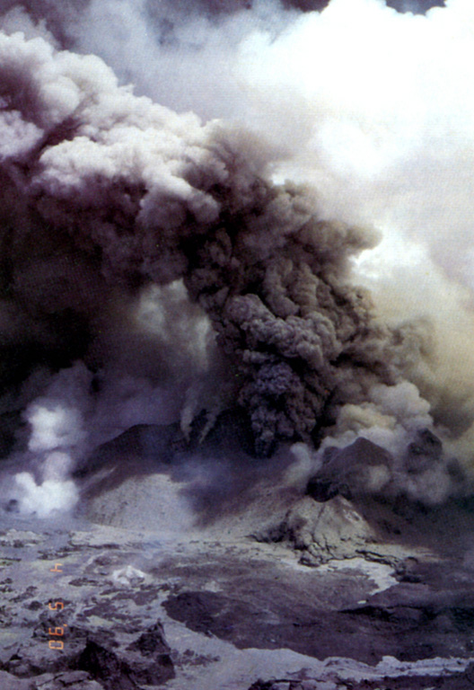 An ash plume rises above vents in the summit crater of Poás volcano on May 4, 1990, near the end of an eruptive period that began in June 1987.  At the time of this photo the crater lake had shrunk substantially to a small feature only several centimeters deep that fluctuated slightly with changes in rainfall recharge.  Lake temperatures were >72°C (measured by infrared thermometer), and small hot springs around the lake had temperatures of 85°C.  Minor explosive eruptions at Poás continued into the following month. Photo by Jorge Barquero, 1990 (Universidad Nacional Costa Rica).