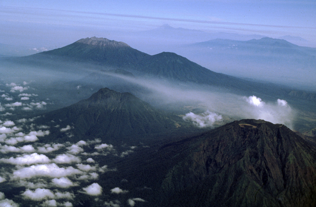 Raung volcano, with its unvegetated summit caldera and Suket peak to the NE, is at the upper left in this aerial view from the eastern tip of Java. In the foreground are Gunung Rante (left-center) and Gunung Merapi (lower right), constructed near the margin of the Ijen caldera complex. The Semeru-Tengger caldera complex is on the far right-center horizon, and the Iyang-Argapura complex is on the upper right. Photo by Lee Siebert, 2000 (Smithsonian Institution).