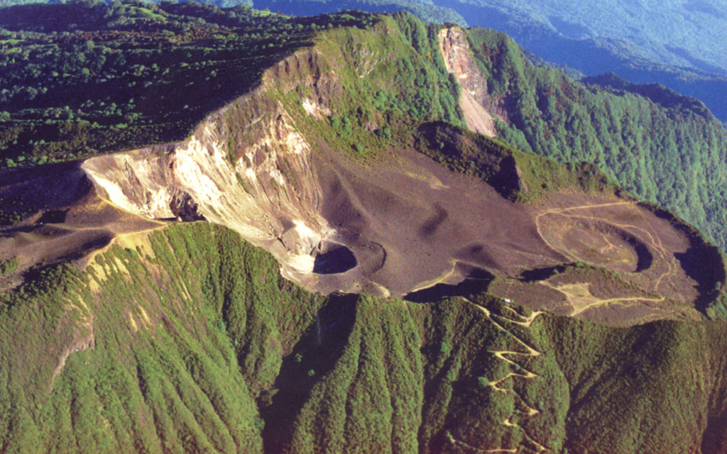 A broad depression breached widely to the NE (right) cuts the summit of Turrialba, the easternmost Holocene volcano in Costa Rica.  The upper part of the depression is partially filled by a smaller edifice with a roughly 1.3-km-wide crater, within which three smaller craters aligned NE-SW have formed.  The three young craters erupted during the 18th-19th centuries; the walls of the two SW-most craters display broad areas of light-colored, hydrothermally altered rocks.  Fumarolic activity continues at these craters. Photo by Federico Chavarria Kopper, 1999.