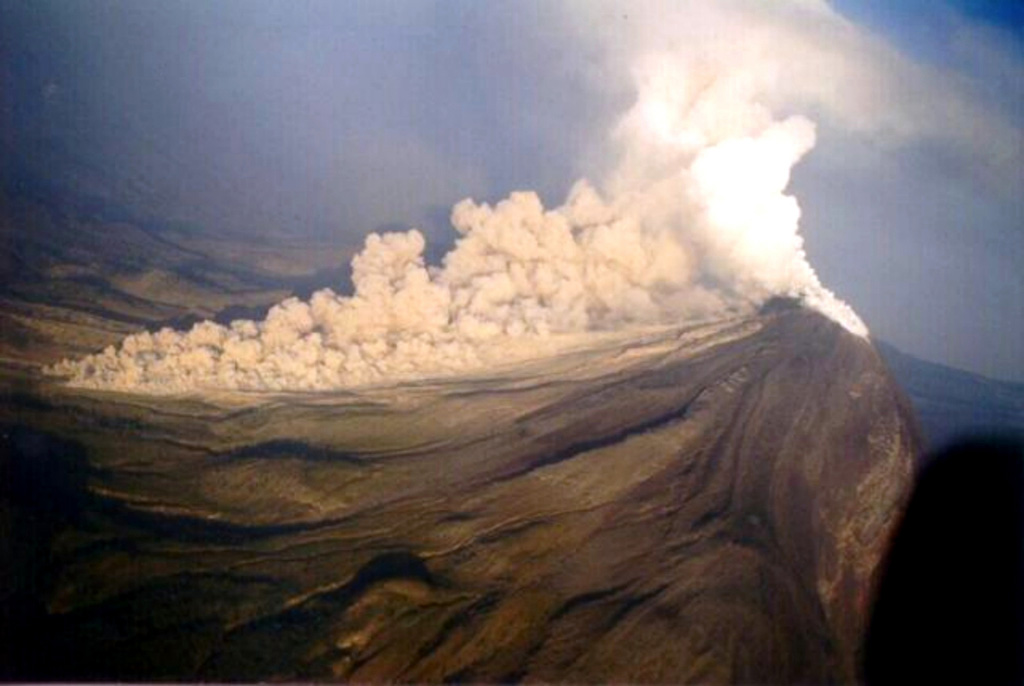 An oblique, wide-angle aerial photo taken with the camera somewhat tilted (note horizon at right-center) shows a pyroclastic flow descending the western flank of Colima at 0830 on November 22, 1998.  The new growing lava dome had almost entirely filled the 1994 crater by the morning of the previous day, after which lava started spilling out of the summit crater area and producing block-and-ash flows at 3-5-minute intervals that mostly traveled south within the eastern branch of Barranca El Cordobán to distances of more than 4 km.   Photo courtesy of Abel Cortés, 1998 (Colima Volcano Observatory, Universidad de Colima).