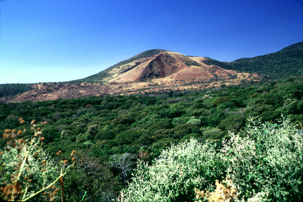 San Marcelino cinder cone (center) on the NE flank of Santa Ana volcano was the source of a basaltic-andesite lava flow that traveled 13 km to the east (left).  Larde (1923) considered the 1722 lava flow to have originated from Izalco volcano, but most other sources place the birth of Izalco in 1770 and assign the 1722 eruption to San Marcelino.  The 1722 lava flow originated from two vents at the eastern and western sides of San Marcelino. Photo by Lee Siebert, 2002 (Smithsonian Institution).
