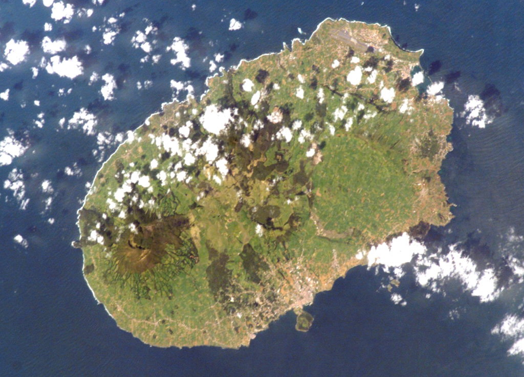 Terceira Island, seen here from the Space Shuttle, contains four stratovolcanoes constructed along a prominent ESE-WNW-trending fissure zone cutting across the island.  The summit caldera of Santa Barbara, the westernmost volcano (and the only one active during historical time) is the dark-colored area at the left.  Cinco Picos caldera can be faintly seen at the center, with the broad Guilherme Moniz caldera at the right.  Historical eruptions have taken place from the rift zone and offshore vents. NASA Space Shuttle image ISS004-E-10890, 2002 (http://eol.jsc.nasa.gov/).