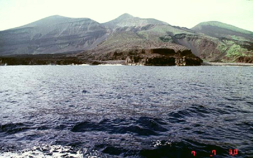 The dark-colored lava flow along the coast in the foreground was emplaced during an eruption that began on 17 August 1939. A new scoria cone (Iwoyama) was constructed in that year at the north end of the 1902 crater. Two lava flows reached the sea, the first at Hyogowan (the bay to the far right) and the second at Chitose Bay. Two people were killed during the eruption, which ceased at the end of December. Copyrighted photo by Akira Takada (Japanese Quaternary Volcanoes database, RIODB, http://riodb02.ibase.aist.go.jp/strata/VOL_JP/EN/index.htm and Geol Surv Japan, AIST, http://www.gsj.jp/).